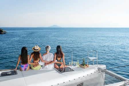 A group of four young women sitting on the edge of the yacht