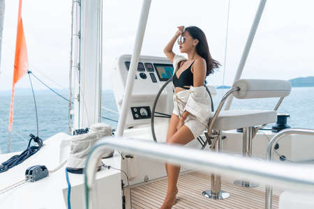Attractive and gorgeous brunette sitting and driving of a modern motor boat.