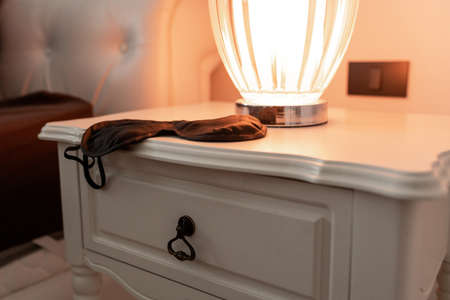 black sleeping mask lying on a white bedside table with a turned on table lamp Imagens