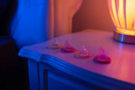 A bunch of condoms lying in a row open, lie on a bedside wooden table near the lamp