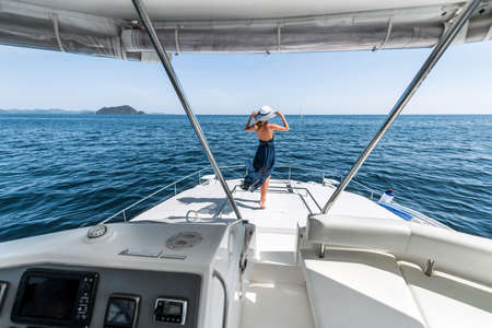 a young girl in a blue dress is standing, raising her hands on the edge of the yacht Banco de Imagens
