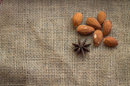 anis: almonds with anis on sacking background. Stock Photo