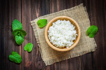 white rice: White rice in a bowl on a wooden background. Stock Photo