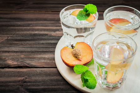 Water with peaches on a wooden background.