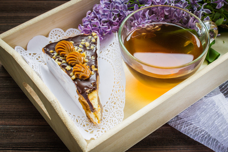 Piece of cake, cup of tea and lilac in a tray on a brown wooden background Stock Photo