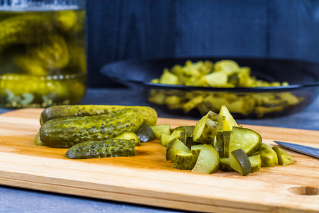 gherkins: Cucumbers or pickled gherkins with a knife on a wooden cutting board. Blue gray background. Bank with cucumbers Stock Photo