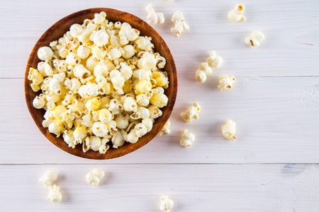 Salty popcorn in a wooden cup is on a white table. Popcorn lies around the bowl. Top view