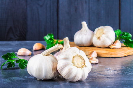 Garlic cloves and garlic bulb on a wooden board on a gray background Stock Photo