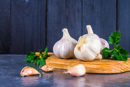 spiciness: Garlic cloves and garlic bulb on a wooden board on a gray background Stock Photo