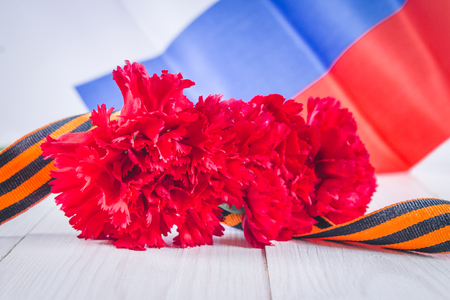 soviet flag: Carnation and ribbon of St. George, as a symbol of victory against the background of the Russian flag. May 9, the day of victory