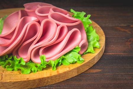 Sliced sausage with salad on a round wooden board Stock Photo - 78161854