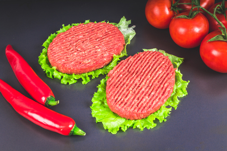 Raw burgers with lettuce on a gray background. Tomatoes, peppers chilli Stock Photo