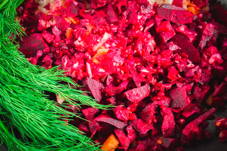 roasting pan: Carrots, beets and onions in a frying pan, around dill, on a brown wooden background. Ingredients for borsch