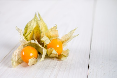 Exotic berries physalis on a white wooden table