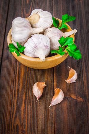 spiciness: Garlic cloves and garlic bulb in a wooden bowl