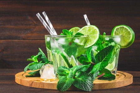 cocktail mixer: Mojito with mint and lime in a glass and a jug on the round board. Brown wood background Stock Photo
