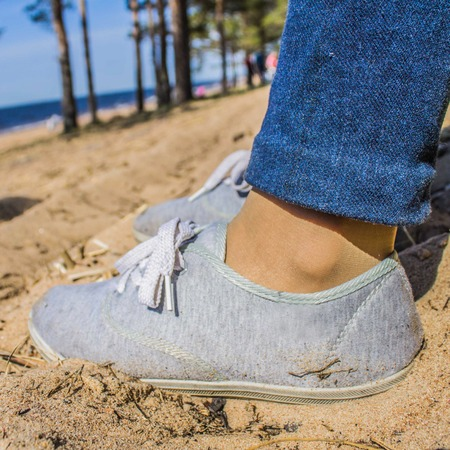 Legs in jeans and sneakers on the sand.