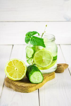 Sassy diet water. Cucumber, lemon, mint lemonade in glasses on white wooden table