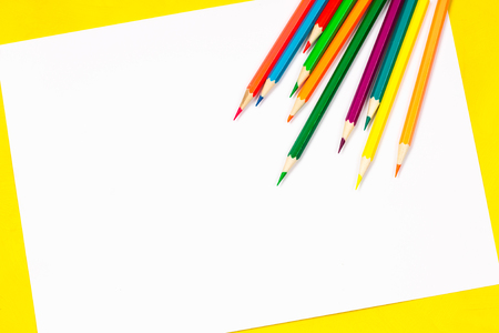 School supplies and white sheet on a bright yellow background, ready for your design.