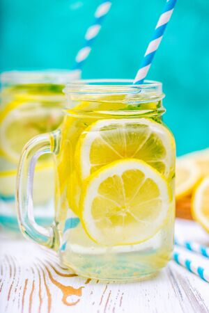 Banks with handles with cold lemonade on a white wooden background. Lemons. Stock Photo