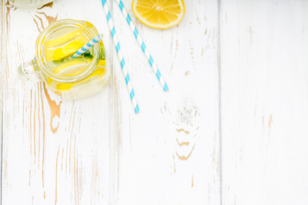 Banks with handles with cold lemonade on a white wooden background. Lemons. Top view.