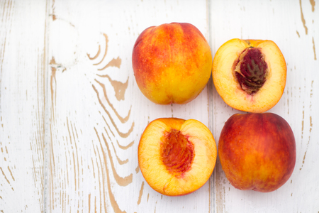 a lot of fresh peaches on a white table. Top view. Stock Photo