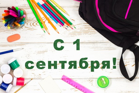 The inscription in Russian is September 1. School supplies on a white wooden background with an empty space for inscriptions
