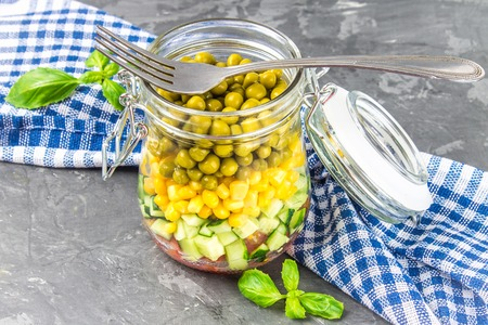 red quinoa: Healthy homemade salad in a jar with vegetables, cucumbers, tomatoes, peas and corn - Healthy diet, detox, pure food or vegetarian concept Stock Photo