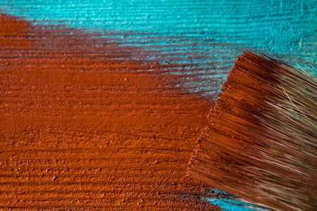 Brush with paint in hand. A man paints blue boards in a brown paint brush. Banco de Imagens
