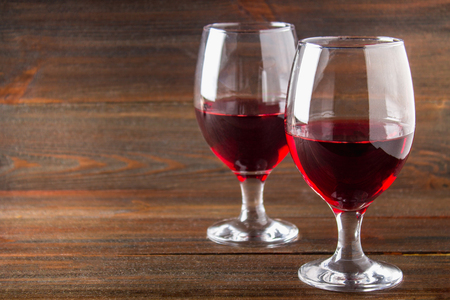 Two glasses of red wine on a brown wooden table. Alcoholic beverages. Stock Photo