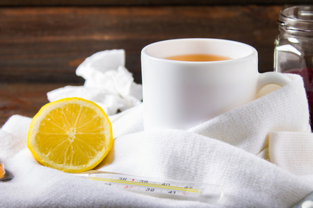 Drugs for colds - pills, spray. Folk remedies - lemon, tea, raspberry jam. Thermometer, handkerchiefs. Treatment of illness, influenza. Warm scarf around the cup.