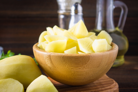 cleared: Raw peeled and sliced potatoes on an old weathered wooden table Stock Photo