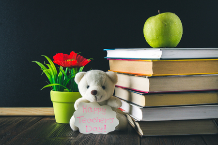 Concept of Teachers Day. Objects on a chalkboard background. Books, green apple, bear with a sign: Happy Teachers Day, pencils and pens in a glass, twig with autumn leaves.