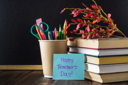 Concept of Teacher's Day. Objects on a chalkboard background. Books, green apple, plaque: Happy Teacher's Day, pencils and pens in a glass, sprig with autumn leaves. Stock Photo - 87181632