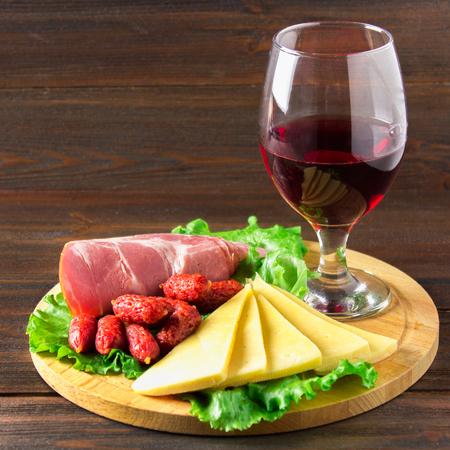 charcutería: El vino tinto con el surtido de embutidos en el fondo
