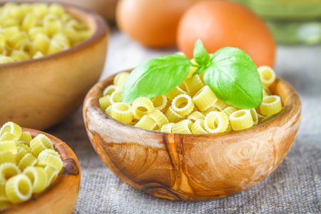 desk: Ditalini macaroni. Pasta rings. Tubettini and thimbles. Anellini. Stock Photo
