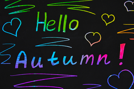 Black plate with colored text. The inscription is hello autumn Stock Photo