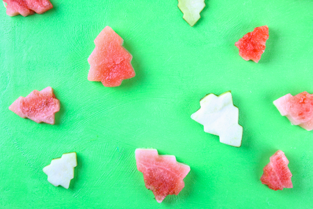 Watermelon in the form of Christmas trees on a green background. Flat lay. Top view