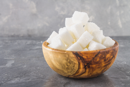 wooden bowl with white sugar cubes on dark background