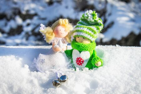 Toy wooden girl in Scandinavian style in knitted green clothes on the snow and angel. Christmas toys