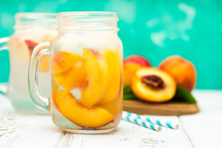 Homemade iced lemonade with ripe peaches. Fresh peach ice tea in a mason jar