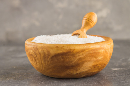 White sugar sugar in a wooden plate with a dustpan on a dark background