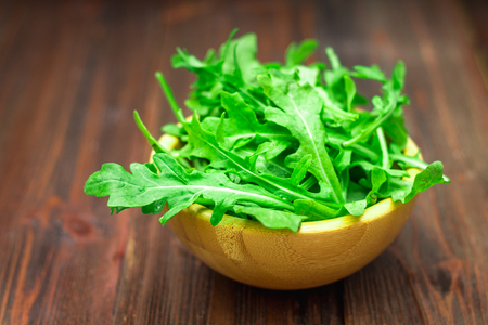 Fresh juicy leaves of arugula on a brown wooden table