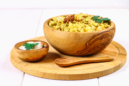 Indian biryani with chicken, yogurt and spices in a plate on a wooden table. New Year's, Christmas dish Imagens
