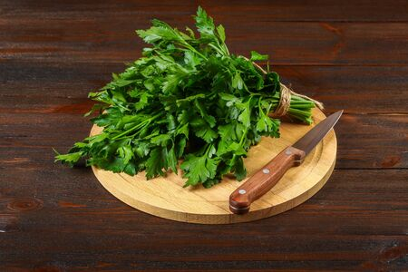A bunch of green parsley on a wooden table with a knife