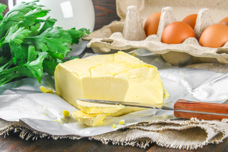 A bar of butter is cut into pieces on a wooden board with a knife, surrounded by milk, eggs and parsley on a brown table. Ingredients for cooking