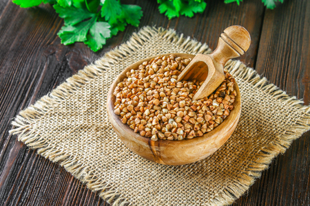 Raw buckwheat in wooden bowls and a scoop on sackcloth on a wooden background. Healthy diet food