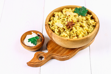 Indian biryani with chicken, yogurt and spices in a plate on a wooden table. New Year's, Christmas dish Stock Photo