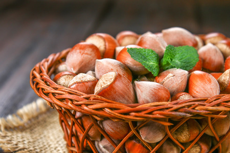 Walnut hazelnuts in a wicker basket on a brown wooden table Foto de archivo