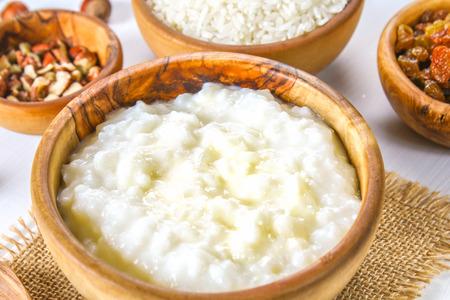 Porridge di latte di riso con noci e uvetta in ciotole di legno su un tavolo di legno bianco Archivio Fotografico